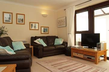 Leather sofas in the living space, looking out onto mature woodland.