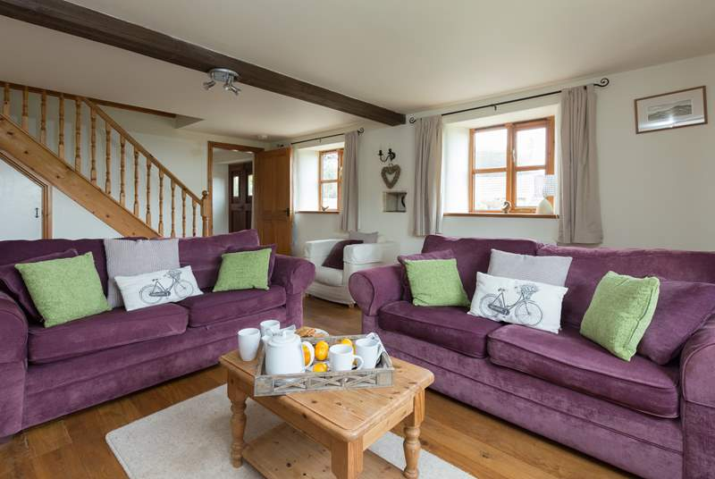There is a spacious living-room with comfortable sofas and a wood-burner effect electric stove in the fireplace.