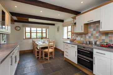 The farmhouse-style kitchen has flagstone floors and is equipped as a home-from-home.