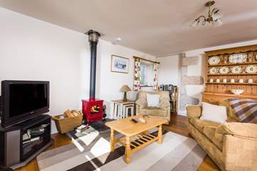 The comfy sofas and armchairs surround the wood-burner.