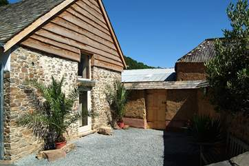The courtyard at the side of the cottage is surrounded by a tile-topped, traditionally constructed cob wall, and leads round to the back garden.
