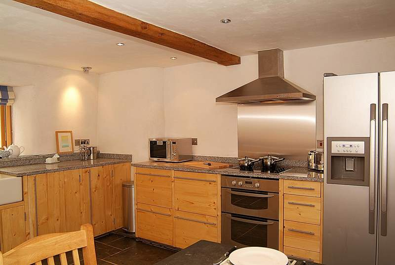 Extremely well-equipped, the kitchen boasts a huge American-style fridge and bespoke wooden kitchen units.