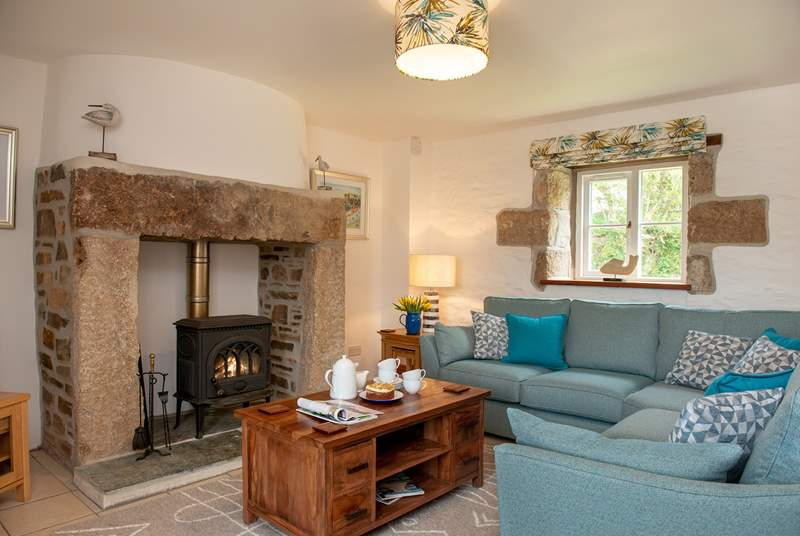 The lovely sitting-room with comfy sofas around the wood-burner.