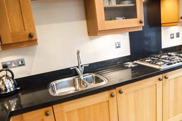 Granite work surfaces and oak units show the quality of the kitchen.