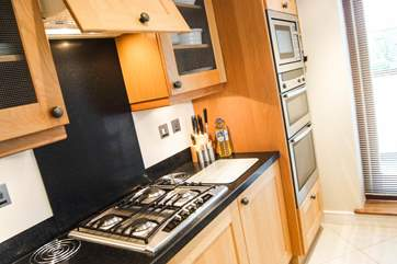 The fully equipped kitchen has gleaming stainless steel appliances with a double oven, built-in microwave and gas hob.