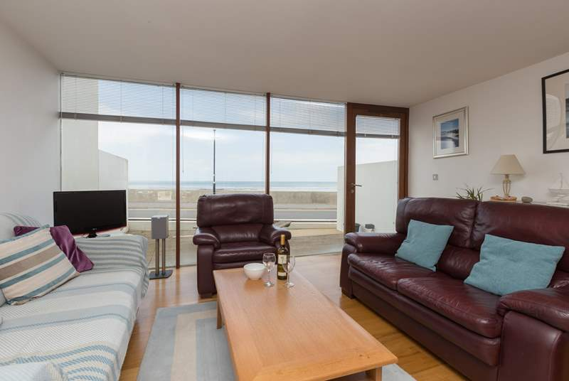 The open plan living space has floor to ceiling glass and a door to the open fronted patio - great for people watching and of course sea views.