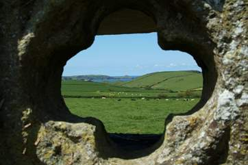 A view of the coastline at Rumps Point, looking through one of the decorative quadrofoils outside the cottage.