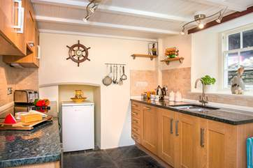 The cottage kitchen has original slate floors and granite worktops.
