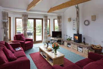 The sitting-room has French doors onto the rear terrace and the wood-burner makes it a great place to stay any time of year.