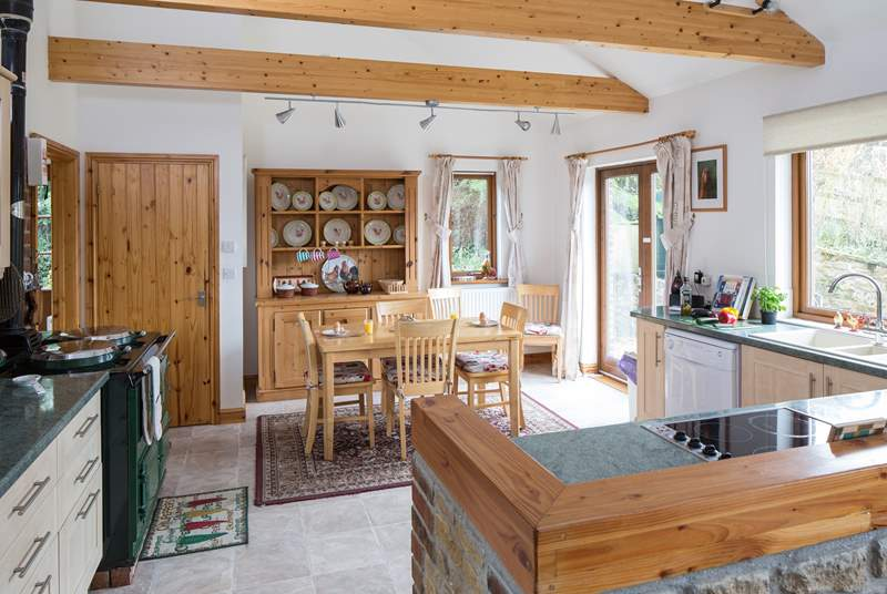 The open plan kitchen/dining-area has a working Aga and modern electric hob.