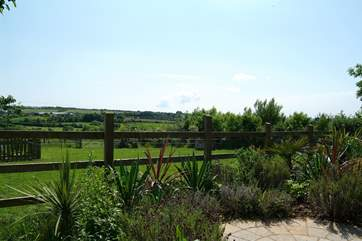 The back garden looks out across the Owners' paddock towards the countryside beyond.