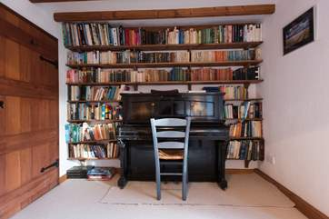 The ground floor bedroom houses a piano and plenty of reading material.