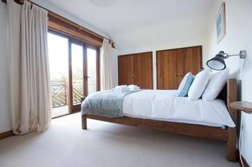The master bedroom boasts a balcony complete with sea views.
