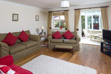 There are three comfortable sofas to choose from at one end of this spacious sitting/dining room.