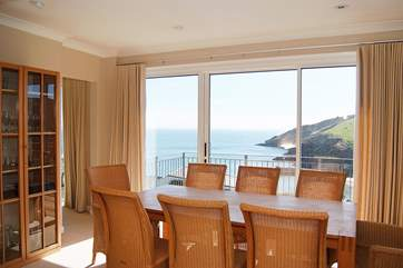 The dining-table is set before the patio doors which lead out to the balcony.
