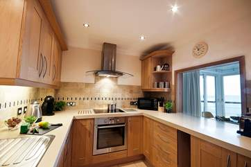 Cream granite worktops and the sea view make working in the kitchen a pleasure.