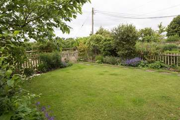 The enclosed front garden has beautiful flower borders and shrubs.