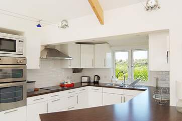 The white high gloss kitchen is beautifully fitted and well-equipped.