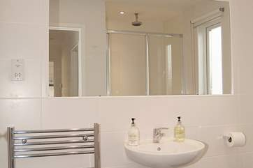 The stylish black and white family shower-room has a double shower cubicle and under-floor heating.