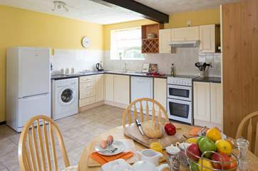 The bright kitchen with dining-area has plenty of space.