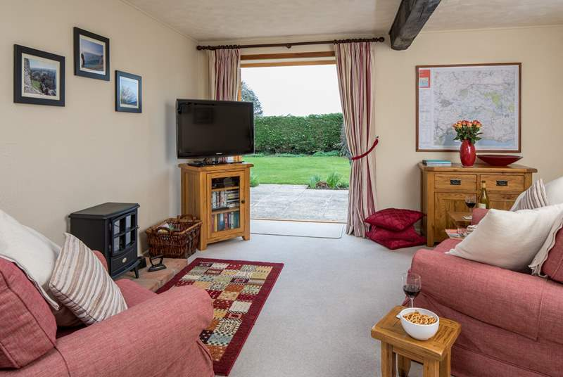 The spacious sitting-room has French windows which open onto a lovely private patio.