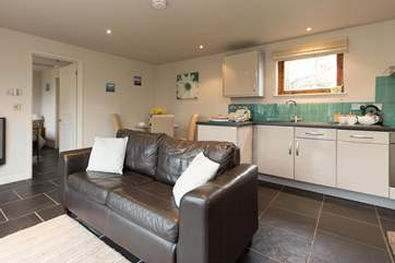 There is a lovely bright open plan living room with dining and kitchen areas.