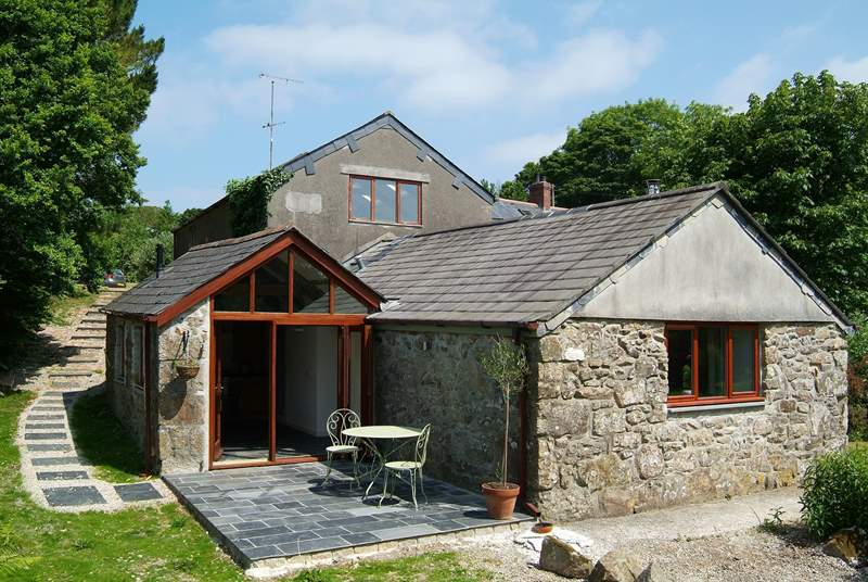 The exterior of the cottage, accessed by steps down from the parking-area.