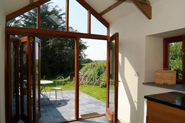 Folding French doors open onto the sunny private patio outside.