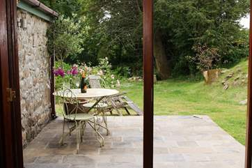 Folding French doors open onto the sunny private patio outside, a lovely place to sit and relax over a meal or simply to read the latest best seller in this peaceful setting.