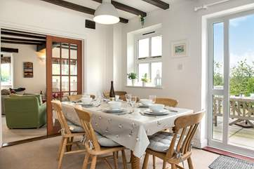 The dining room sits between the kitchen and the sitting room, with doors out to the dining terrace