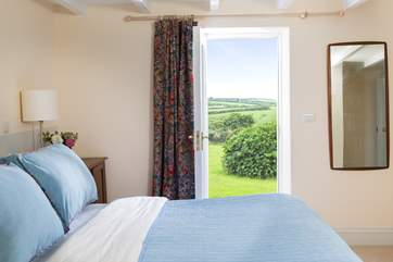 The master bedroom enjoys views from the window and door onto the garden and countryside beyond.