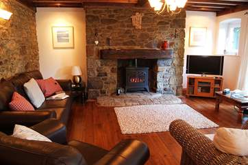 The sitting/dining-room has comfy seating for all around the stone fireplace.