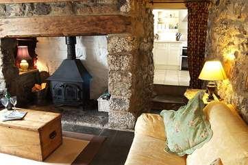 The sitting-room has a cosy wood-burner in the inglenook fireplace and comfy sofas.