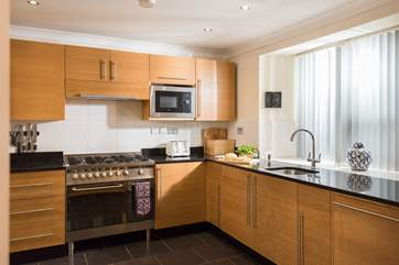 Granite work surfaces and solid wood units show the quality of the apartment.
