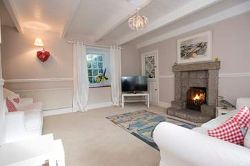 The second sitting-room with a TV and roaring open fire.