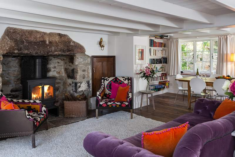 The main sitting-room with a roaring fire and dining-area.