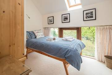 This light filled single bedroom looks over the garden at the back of the cottage.