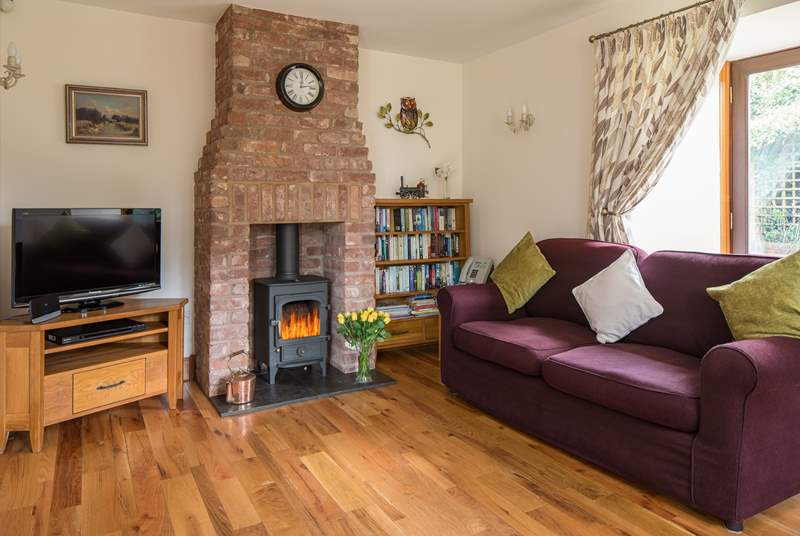 The dual-aspect sitting/dining-room has doors out to the garden and a wonderful wood-burner for cosy evenings in. There are two sofas to snuggle up on.