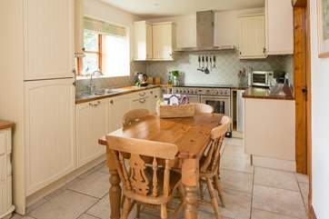 The well-equipped kitchen has a welcoming farmhouse style table seating up to six guests comfortably.