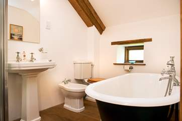 The en-suite bathroom has a double ended roll top bath with a separate shower cubicle
