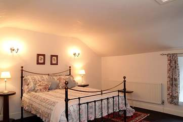 The spacious main bedroom has a 5' bed and plenty of space for a cot.