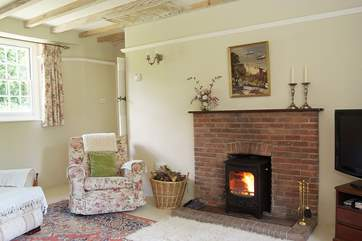 Comfortable armchairs flank the wood-burner.