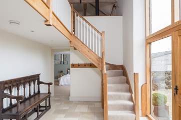 Steps lead from the front door to the open plan first floor in this reverse-level barn conversion. The master bedroom is in the background.