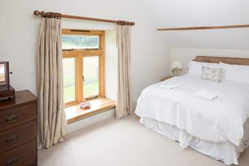 The master bedroom looks out over the little lane to the fields beyond.