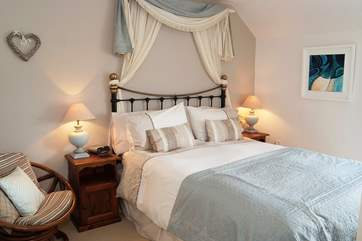 The master bedroom with king-size bed is beautifully furnished.