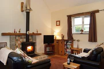 Two leather sofas face the welcoming wood-burner.