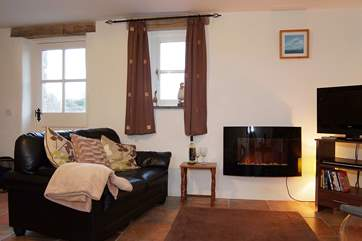 The comfy living-room includes a wall-mounted fire, great for those cooler evenings.