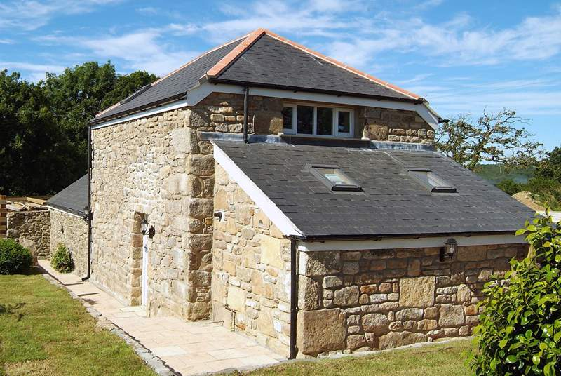 The sunny enclosed garden wraps around the side and rear of this lovely stone barn.