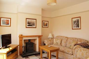 The cosy sitting-room includes a welcoming little wood-burner.