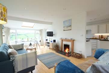 The open plan living-room is flooded with light from the large picture windows.